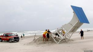 Here lifeguards and firefighters lower a lifeguard stand