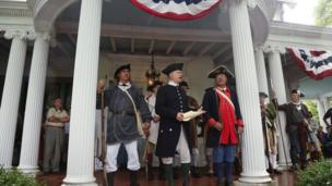Larry Stephan, of Oakland, New Jersey, reads the Declaration of Independence on the porch of Ringwood Manor, as other re-enactors and visitors listen