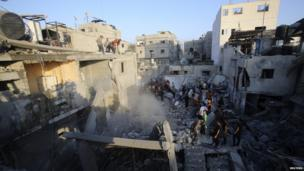 Palestinians and rescue workers stand near rubble of a house which police said was destroyed in an Israeli air strike in Khan Younis in the southern Gaza Strip 10 July 2014.