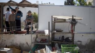 Residents look at damage caused by a rocket fired by Palestinian militants from in side Gaza Strip after it hit in Netivot, southern Israel, 10 July 2014.