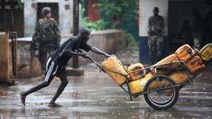 A man pushing cartons through the rain in Bangui, CAR - Tuesday 8 July 2014