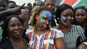 Two women with the South Sudanese flag painted on their faces smile in a crowd in Juba, South Sudan - Wednesday 9 July 2014
