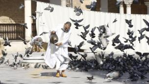 A man feeding pigeon at Zitouna mosque in Tunis, Tunisia - Sunday 6 July 2014