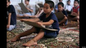 Pupils reading sections of the Koran on boards at a mosque in Algeria - Tuesday 8 July 2014