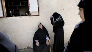 Members of the al-Kaware family grieve during the funeral for seven members of the family who were killed in the Gaza Strip