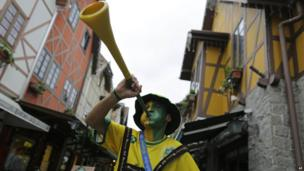 A Brazilian of German descent blows a horn before the World Cup semi-final match between Brazil and Germany in Blumenau, Brazil, Tuesday, July 8, 2014