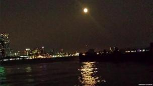 The orange moon sits above an illuminated skyline, next to the ocean, and reflects in the water.