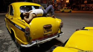 A driver takes a nap on his yellow Ambassador taxi at a roadside during early morning