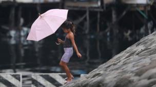 Girl with umbrella in Manila ahead of Typhoon Rammasun