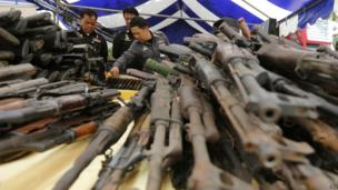 Thai police officers look at seized firearms before they are destroyed