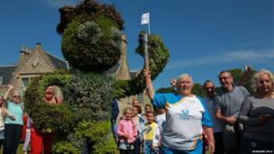 Baton bearer poses next to three metre high shrub pruned to resemble Commonwealth Games mascot Clyde