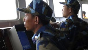 Crewmen aboard Vietnam coastguard ship 8003 look at a Chinese navy frigate on a screen, in disputed waters close to the Haiyang Shiyou 981, known in Vietnam as HD-981, oil rig in the South China Sea on 15 July, 2014