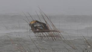 A fisherman's hut in the middle of fish pens is pounded by waves.