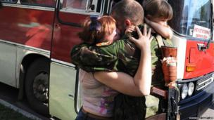 A Pro-Russian militant kisses says goodbye to his family in Donetsk before they board a bus for Russia