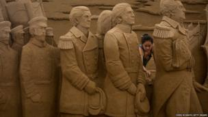 Sand sculptor Sue McGrew of the USA works on a large sand sculpture at the Sand Art Exhibition in Yokohama, Japan.