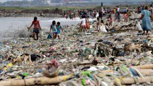 People collect reusable materials from debris washed ashore by Typhoon Rammasun in Manila, Philippines