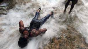 A pilgrim bathes at a waterfall in Saut d'Eau, north of Port-au-Prince, Haiti