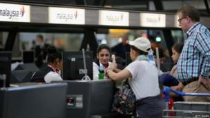 Passengers check in for an Air Malaysia flight at Amsterdam's Schiphol airport (18 July 2014)