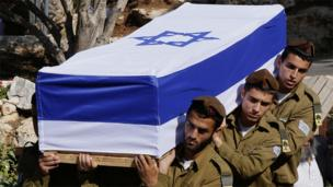 Israeli soldiers carry the flag draped coffin of slain 20-year-old Staff Sergeant Moshe Melako of the Golani Brigade, who was killed the previous day during fighting with of Palestinian militants in the Gaza Strip, on July 21