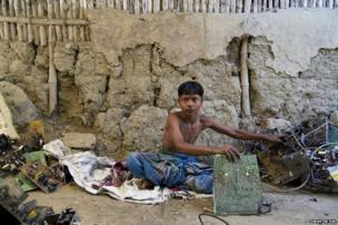 Kochimuni, 15, sits in front of his mud house sorting E-waste and breaking down motherboards into simpler components.