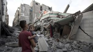 A Palestinian man carrying a child looks at the destroyed house of Hamas top leader in Gaza