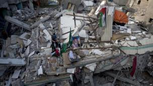 A Palestinian man displays national flags, Islamist Hamas movement flags and portraits of Hamas top leader in Gaza, Ismail Haniya, on the rubble of the latter's house after it was hit by an overnight Israeli air strike, 29 July 2014. in Gaza City.