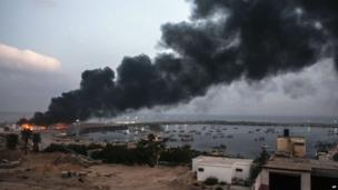 A building within the Gaza port is seen on fire after several strikes early on July 29, 2014.