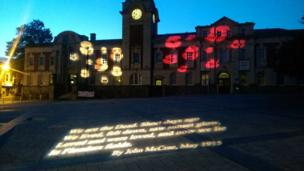 Red and white poppies illuminate the town hall in Barry