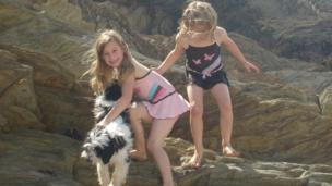 two little girls are climbing some rocks with their pet dog.
