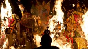"""An Ethnic Chinese priest stands in front of statue made of paper of Chinese deity """"Da Shi Ye"""" or Guardian God of Ghosts set of fire by devotees during the Hungry Ghost festival in Kuala Lumpur, late on 10 August, 2014"""