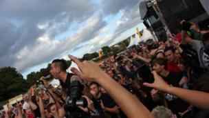 Canwr y band Anti-Flag yn perfformio ymysg y gynulleidfa // The Anti-Flag singer performing amongst the crowd