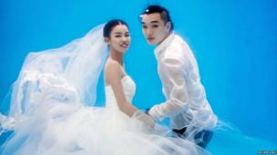 Bride and groom-to-be having their wedding photos taken underwater