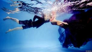 A couple kiss underwater