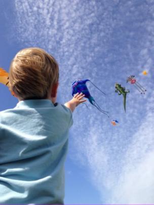 Boy reaching for balloons