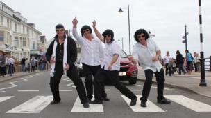 Four Elvis lookalikes on a road crossing