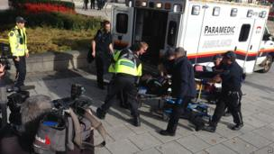 Police and medical personnel move a wounded person into an ambulance at the scene of a shooting at the National War Memorial in Ottawa