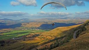 Hand gliders over the Rhigos Mountain, Rhondda Cynon Taff with the Brecon Beacons in the background.