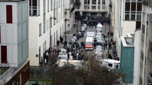 A general view shows firefighters, police officers and forensics gathered in front of the offices of the French satirical newspaper Charlie Hebdo in Paris
