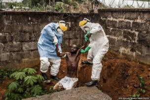 Medical staff at the Hastings Ebola Treatment Centre work to escort a man in the throes of Ebola-induced delirium back into the isolation ward from which he escaped