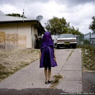 Laurinda waits in her purple dress for the bus that will take her to Sunday School.