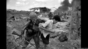Milwr Americanaidd yn arestio bachgen ifanc o Fietnam ger Saigon // US soldier arresting a Vietnamese youth on the outskirts of Saigon. 1968