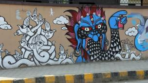 One of these deities is pictured spray-painting graffiti.