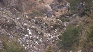 A screen grab taken from an AFP TV video on March 24, 2015 shows search and rescue personnel near scattered debris while making their way through the crash site of the Germanwings Airbus A320