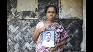 Sabitri Mondal holds picture of her husband who was killed by a tiger