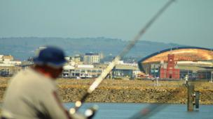 Cardiff Bay as a fisherman looks on.