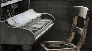 Piano and chair in a derelict house