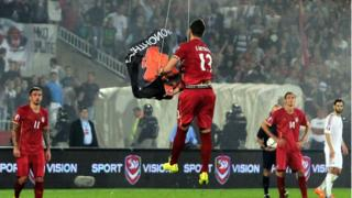 Serbia defender Stefan Mitrovic grabs flag suspended from drone on 14 Oct 2014