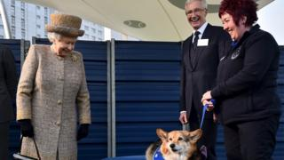 The Queen looks at a corgi at Battersea Dogs and Cats Home in March 2015 as TV presenter Paul O'Grady looks on