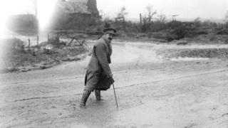 Muirhead Bone crossing a muddy road in France, 1916