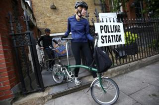 伦敦阿森纳某投票站两名选民推着自行车离开(8/6/2017)